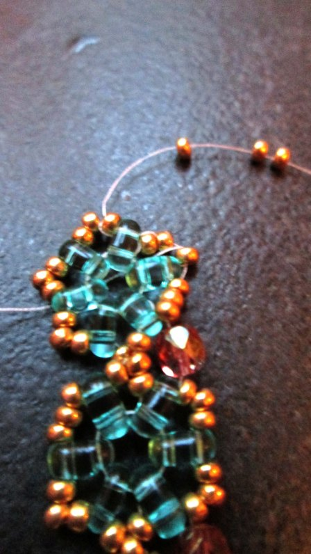 Go through all the seed beads down each side , adding a crystal into the gap between each motif. At the end come out of the first seed bead, add 3 more on and go back into the third seed bead. Go back down the other side.