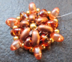 Again, bring the thread up to the top hole, add on a size 11 seed bead, another twin and a size 11 seed bead between each existing twin bead.