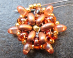 Go around the last round again to secure it. Finish with the thread coming out of a twin bead, add three size 11 sized beads and go through the seed bead, twin and seed bead from the previous row.