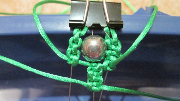 Moving one bead up and then 6 square knots on the centre thread.
